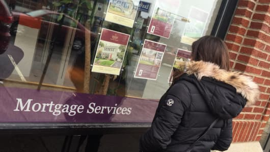A woman looks at real estate listings outside a Berkshire Hathaway Home Services office in Montclair, N.J.
